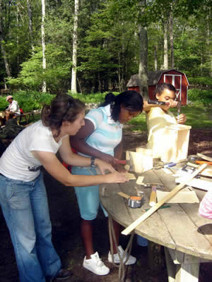 Emily, our woodworking instructor, helps Troi with her project